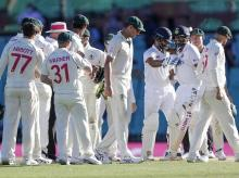 R Ashwin and Hanuma Vihari react as Australian players look on at the end of play on the final day of the third cricket test between India and Australia at the Sydney Cricket Ground