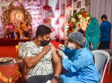 A health worker gives a visitor at a Ganpati pandal in Mumbai a dose of a coronavirus vaccine on September 15, 2021. (PTI photo)