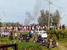 A vehicle set ablaze after violence broke out after farmers agitating were allegedly run over by a vehicle in the convoy of a union minister, in Lakhimpur Kheri