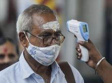 A health worker checks the body temperature of a traveller as a safety measure against the coronavirus before allowing him to proceed at a railway station in Mumbai on October 9, 2021. (PTI Photo/Kunal Patil)