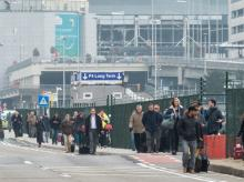 People walk away from Brussels airport after explosions rocked the facility in Brussels, Belgium