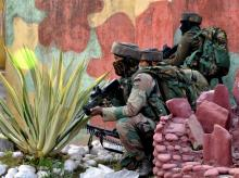 Security personnel takes positions during a militants attack Sunjuwan Army camp in Jammu