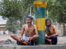 File photo | Two men cool-off themselves under public water taps, during a hot summer afternoon, in Amritsar.