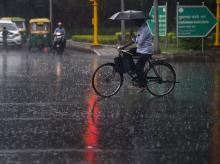 A cyclist crosses a road during monsoon rainfall at Zakir Hussain Marg, in New Delhi