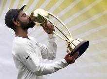 Virat Kohli kisses the Border-Gavaskar Trophy as he celebrate their series win over Australia