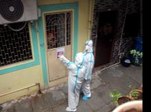 Health workers wear protective gear on their way to take health details of the residents of a 'containment zones' at the Kajupada area in Mumbai