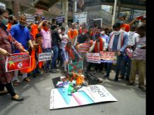Swadeshi Jagran Manch workers hold a placard and burn Chinese products as they protest against Chinese goods and against the killing of Indian soldiers during India China clash, at Laxmi Nagar in New Delhi