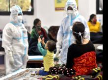 Health workers in PPE kit playing with a child at the Commonwealth Games (CWG) Village sports complex, temporarily converted into a COVID care center, in New Delhi.